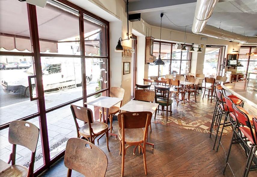 Foto del locale visto dall'interno con vetrata e tavolini.