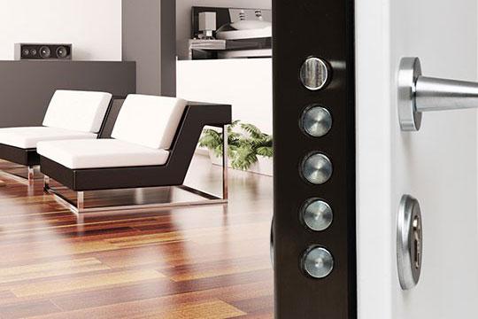 Porta blindata semi aperta che mostra l'interno di un'abitazione. In primo piano i 4 perni della serratura sul lato interno della porta.