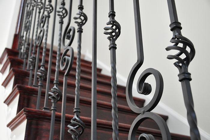 Foto di un particolare di una ringhiera in ferro con scala interna. LA ringhiera è decorata con eleganti volute e pigne.
