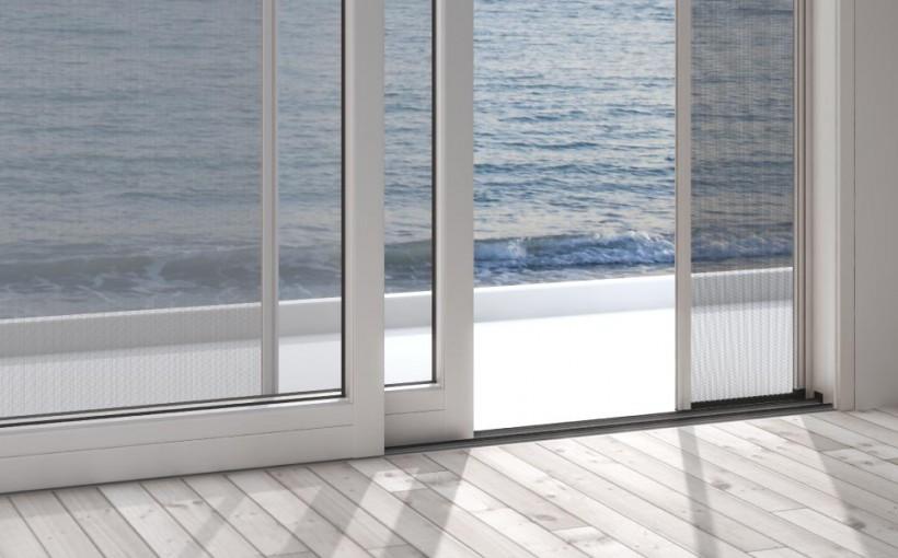 Foto di una zanzariera aperta di una finestra di un appartamento lungo il mare.